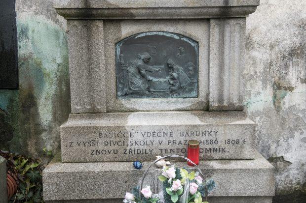 Detail náhrobku Boženy Němcové. Reliéfní plaketa zobrazuje Babičku, jak ukazuje vnoučatům tolar obdržený od císaře Josefa II. Písmo na pomníku navrhl Josef Mánes.
